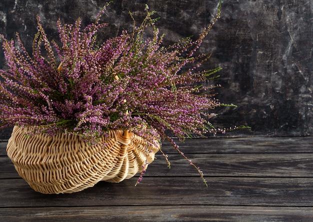 Kosz z kwiatami na czarnym tle liliowy wrzos
