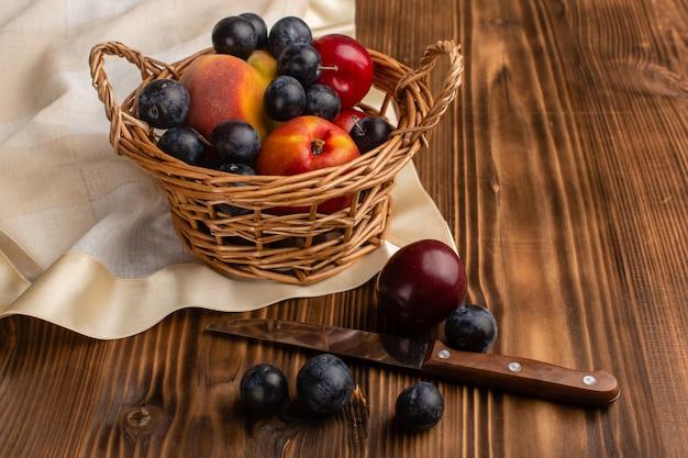 Kosz z owocami tarniny śliwki i brzoskwinie na drewnie