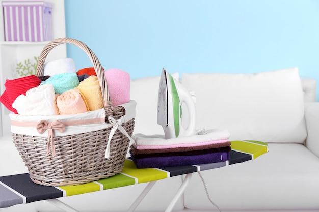 Kosz z praniem i deską do prasowania na tle wnętrza domu