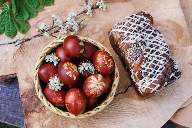 Kosz z tortem wielkanocnym i czerwonymi jajkami na rustykalnym drewnianym stole
