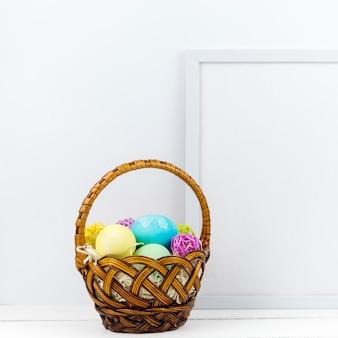 Kosz z wielkanocnymi jajkami blisko obramia na stole