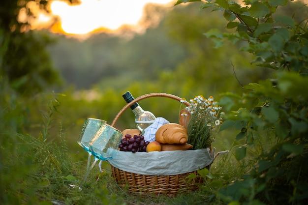 Kosz z winem, chlebem i owocami