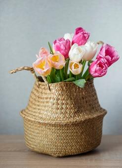 Kosz z wiosennymi kolorowymi tulipanami na stole