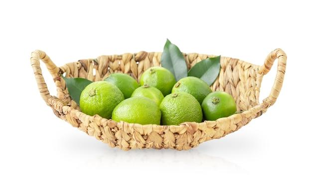 Kosz z zielonymi limonkami i liśćmi na białym tle na białym tle