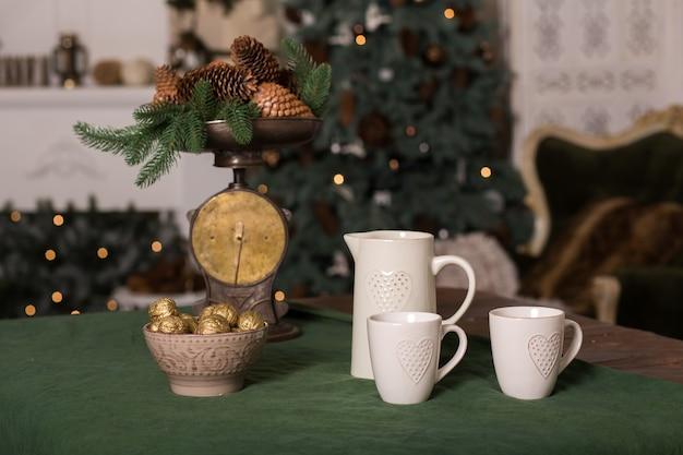 Kosz ze słodyczami zawinięty w folię, na stole obok kompletu do herbaty. zielona choinka z wypukłościami na tle rozmycia. komfort w domu