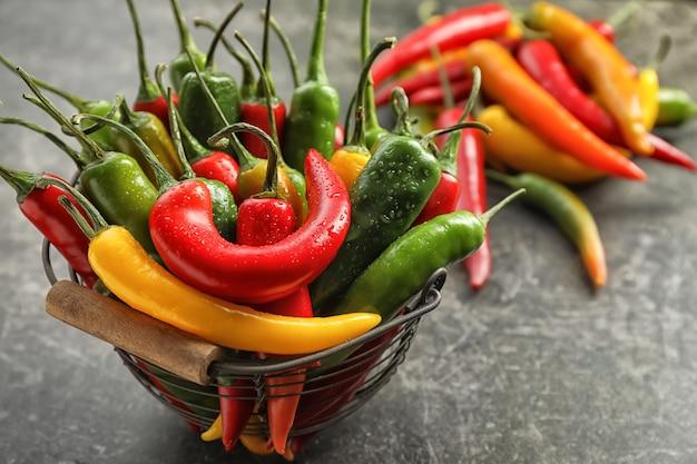 Kosz ze świeżymi papryczkami chili na szarym tle