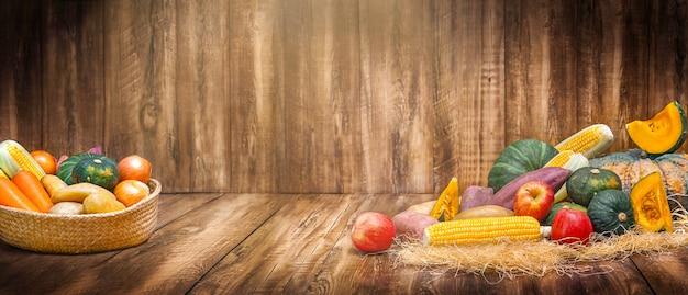 Kosz ze zbiorem warzyw i owoców na drewnianym tle na święto dziękczynienia