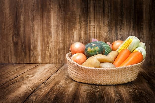 Kosz ze zbiorem warzyw i owoców na drewnianym tle