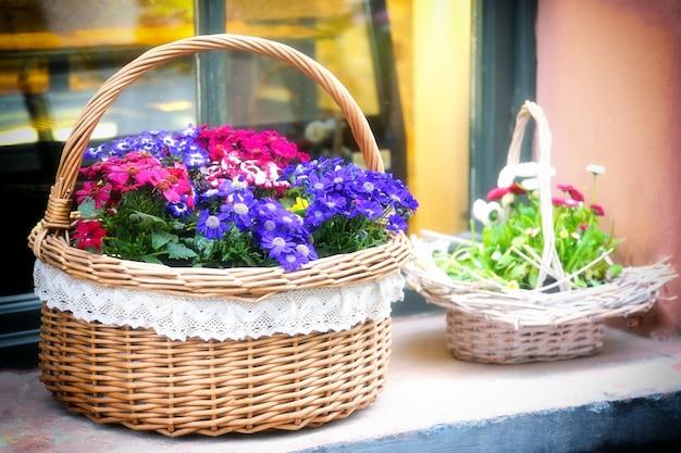 Kosze kwiatów na parapecie.