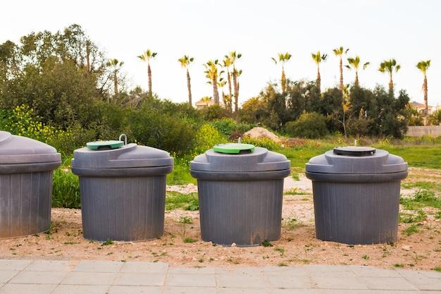Kosze na śmieci miejskie. zielony przepełniony śmietnik