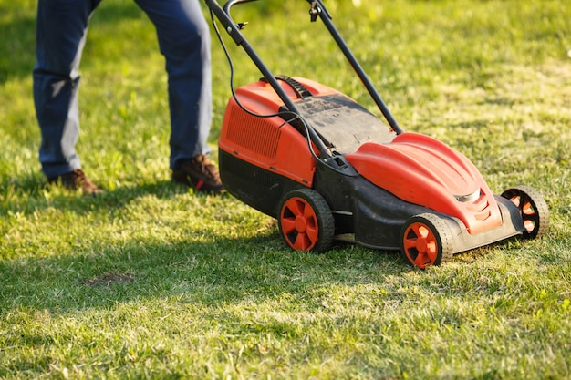 Koszenie trymera - pracownik ciie trawę w zielonym jardzie przy zmierzchem. człowiek z kosiarki elektrycznej, koszenia trawnika. ogrodnik przycinanie ogrodu.