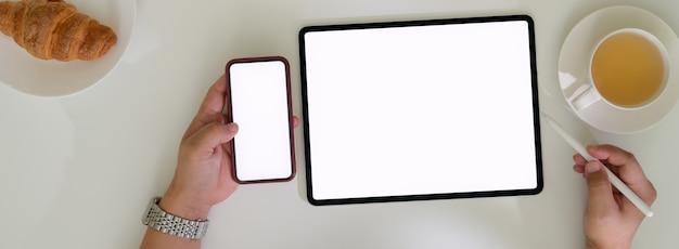 Koszt stały strzelający biznesmen pracuje z pustego ekranu cyfrowymi urządzeniami i ma śniadanie