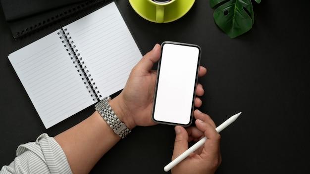 Koszt stały strzelał męski freelancer mienia smartphone podczas gdy relaksujący w ciemnym nowożytnym miejscu pracy