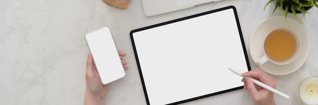 Koszt stały żeński freelancer pracuje na pustym ekranie tabletu i smartfona na marmurowym stole