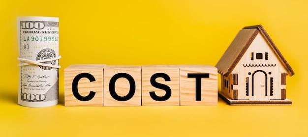 Koszt z miniaturowym modelem domu i pieniędzmi na żółtym tle. pojęcie biznesu, finansów, kredytu, podatków, nieruchomości, domu, mieszkania