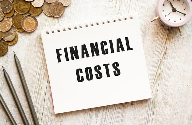 Koszty finansowe tekst na kartce notatnika.