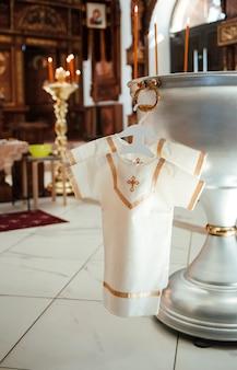 Koszula do chrztu wisi na wieszaku na łaźni w kościele. chrzest dziecka.