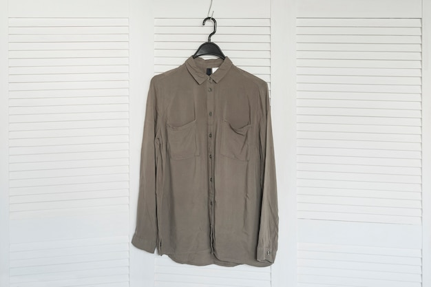 Koszula khaki wisząca na wieszaku. biały drewniany ekran. modna szafa