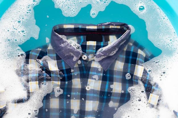 Koszula moczona w rozpuszczonym w wodzie detergentu w proszku. koncepcja pralni
