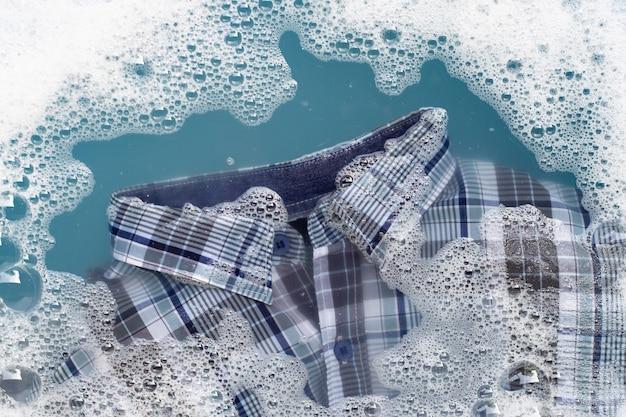 Koszula moczona w rozpuszczonym w wodzie detergentu w proszku
