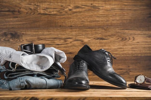 Koszula na dżinsy z paskiem i buty z zegarkiem na drewnianym stole