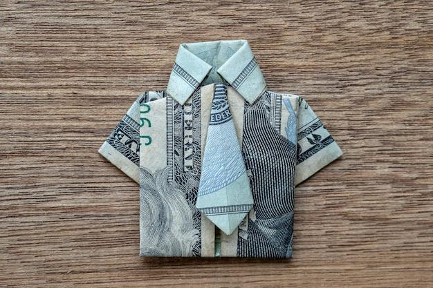 Koszula origami wykonana z banknotu dolara na podłoże drewniane. ścieśniać. koszulka z banknotem dolara