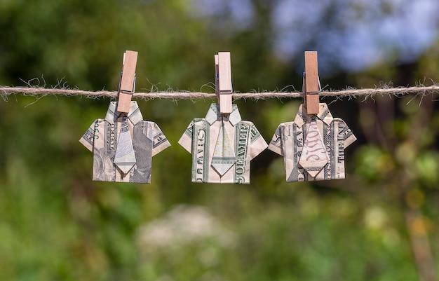 Koszula origami wykonana z banknotu dolara na wiszącym zielonym tle przyrody. dolary wiszące na liny. ścieśniać. koszulka z banknotem dolara