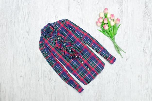 Koszula w kratkę i bukiet tulipanów. modna koncepcja