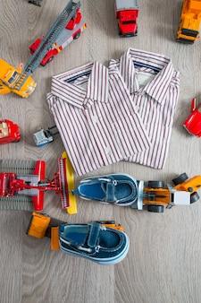 Koszula w paski i niebieskie buty w pobliżu żółtych i czerwonych samochodów