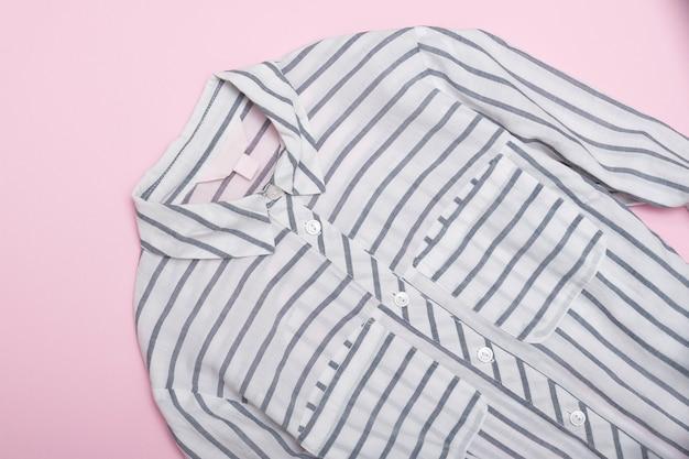 Koszula w paski na różowym tle. modna koncepcja. ścieśniać