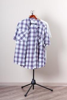 Koszule na wieszakach na białej ścianie w pustym pokoju ekstremalne zbliżenie
