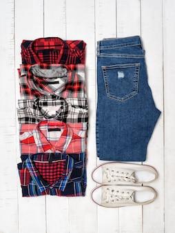 Koszule w kratę, niebieskie dżinsy i białe trampki