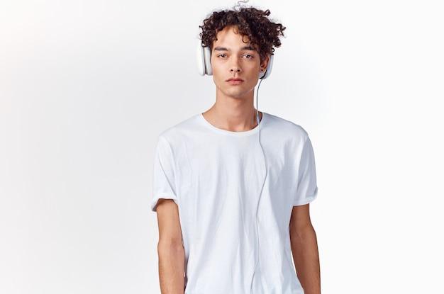 Koszulka młodzieżowa i słuchawki na jasnej ścianie model nowej technologii