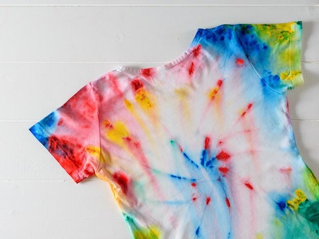 Koszulka pomalowana w barwnik krawatowy na białym drewnianym stole.