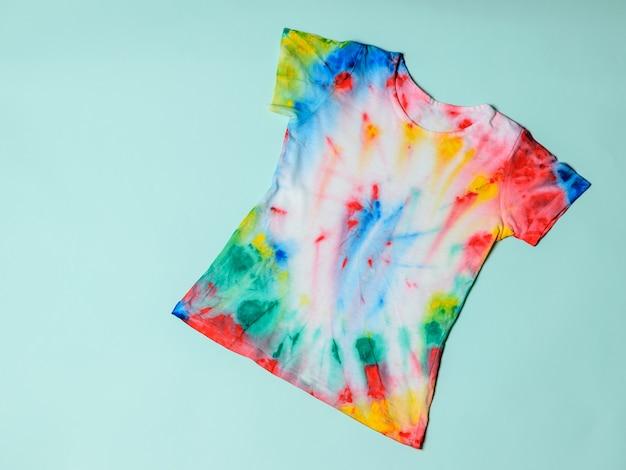 Koszulka pomalowana w barwnik krawatowy na niebieskim pastelowym tle. leżał płasko. widok z góry.