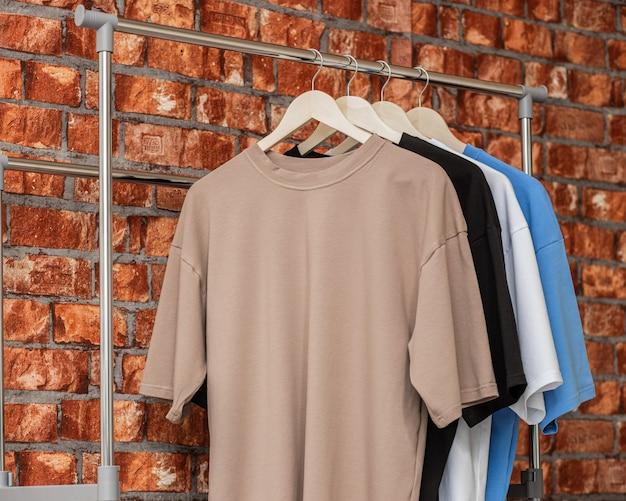 Koszulki dla mężczyzny na drewnianych wieszakach w sklepie z modą