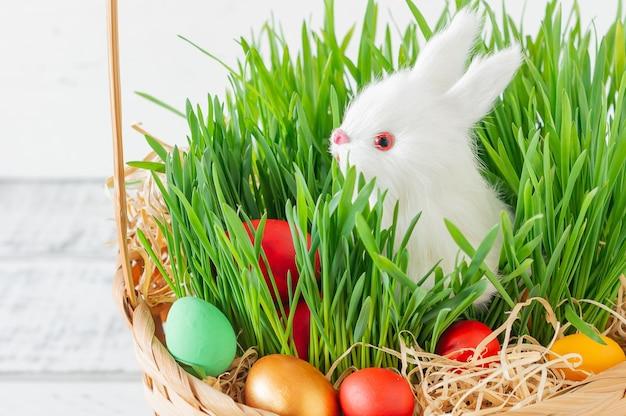 Koszyczek wielkanocny z zieloną trawą wypełnioną kolorowymi jajkami wielkanocnymi i białym królikiem. wesołych świąt wielkanocnych.