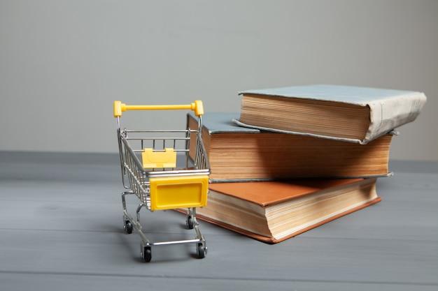 Koszyk i książki na stole. koncepcja kupowania książek na szarym tle