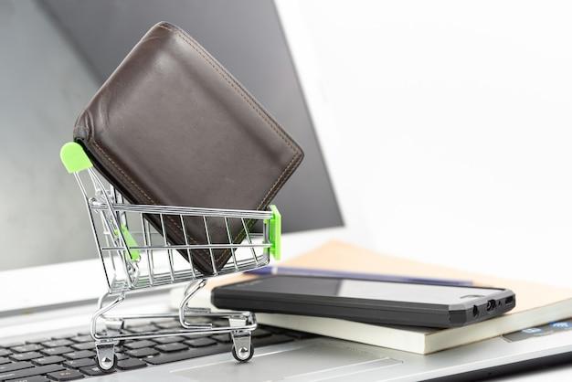 Koszyk i portfel na tle notebooka i laptopa. zakupy online, oszczędność inwestycji, zakup, koncepcja biznesowa.