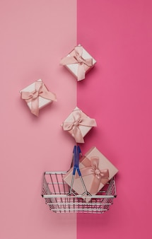 Koszyk i pudełka na prezenty z kokardkami na różowym pastelowym tle. kompozycja na boże narodzenie, urodziny lub wesele. widok z góry