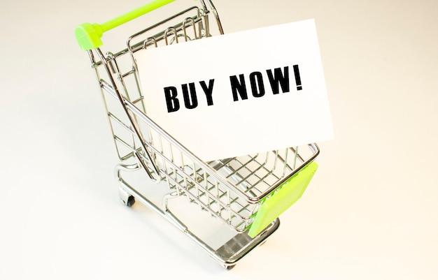 Koszyk i tekst kup teraz na białym papierze koncepcja listy zakupów