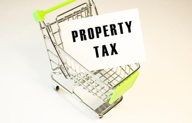 Koszyk i tekst podatek od własności na białym papierze. koncepcja listy zakupów na jasnym tle.