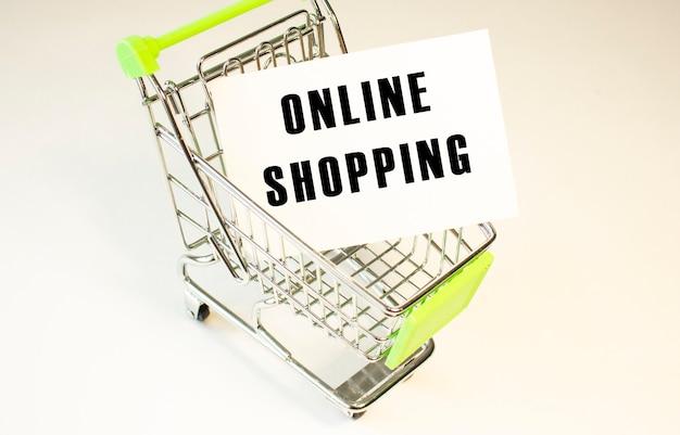 Koszyk i tekst zakupy online na białym papierze