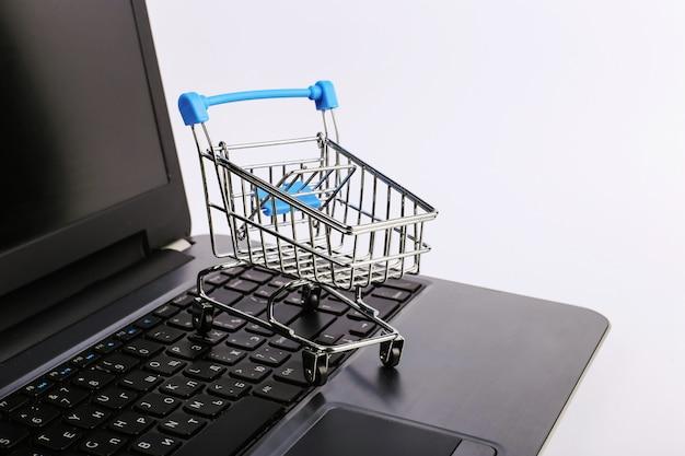 Koszyk jest na laptopie. koncepcja sprzedaży online.