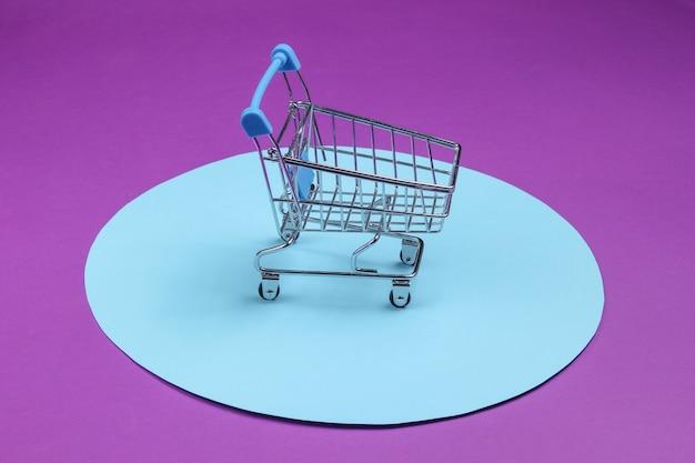 Koszyk na fioletowym tle z niebieskim pastelowym kółkiem. minimalistyczna koncepcja zakupów, zakupoholiczka.