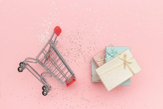 Koszyk, wózek i pudełka z pastelowych kolorach na różowym tle
