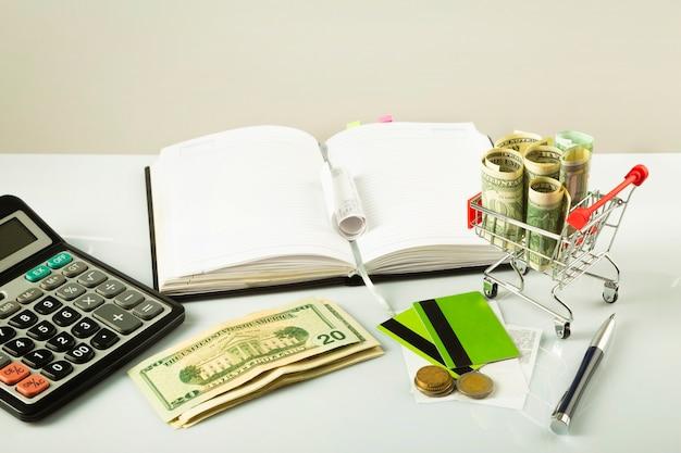 Koszyk z dolarami, kalkulator, notatnik na świetle fone.biznes kantseptsiya.