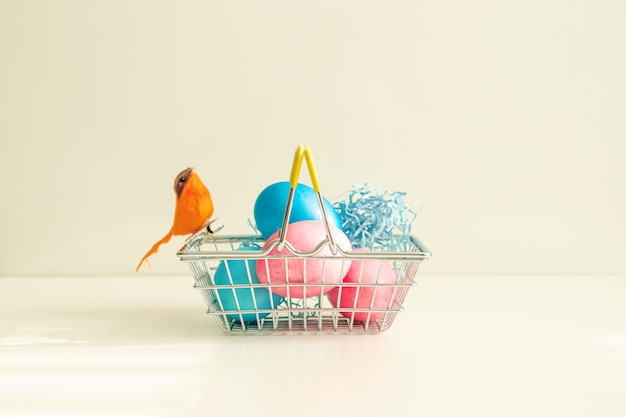 Koszyk z kolorowymi jajkami i pomarańczowym ptaszkiem. koncepcja wielkanocna, wysoki klucz.