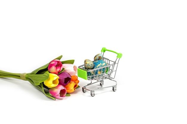 Koszyk z malowanymi pisankami i bukietem tulipanów na białym tle