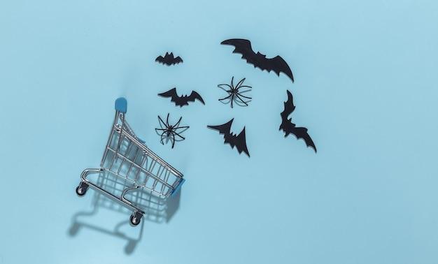 Koszyk z nietoperzami i pająkami na niebieskim jasnym tle. motyw halloween.